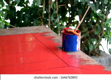 Painting work, painting the table with red paint from blue tin
