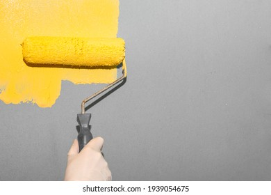 Painting work. A woman paints a gray wall with a roller yellow. Trending colors of the year.