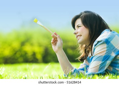 Painting the world. Smiling girl on grass with a paintbrush