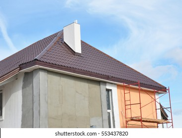 Painting,Plastering, Stucco Exterior House Wall. Facade Thermal Insulation and Painting Repair Works During Exterior Renovations. House Roofing Construction, Soffits and Roof Insulation Repair.