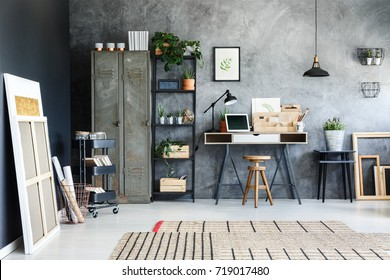 Paintings leaning against black wall in dark atelier with wooden organizer and laptop on desk
