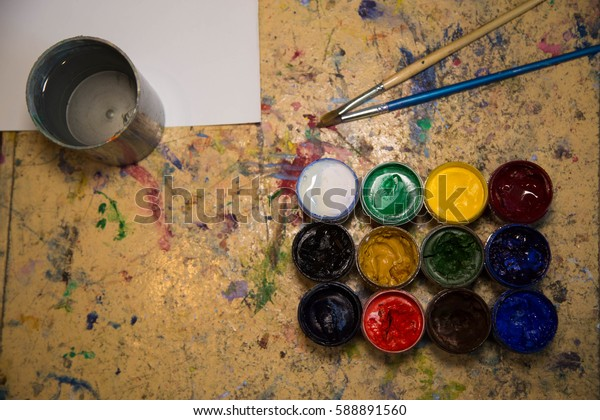 paints and artist's brush on the table
