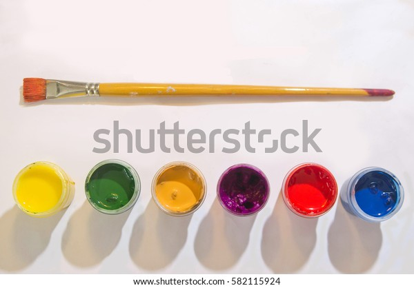 Paints and brushes on the white paper background