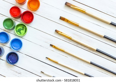 Paints and brushes on a white wooden background