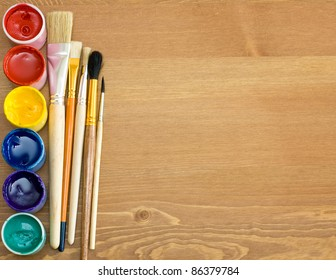 paints and brushes on wooden table