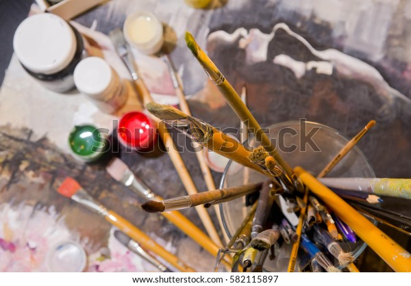 Paints and brushes on the workplace of painter