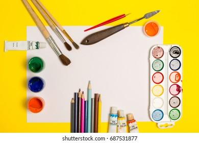 Paints brushes pencils paper colors mock up
