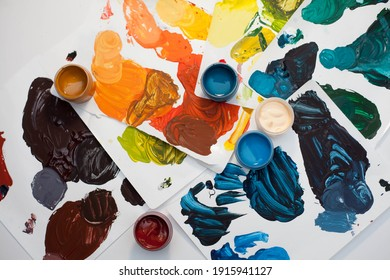 paints and brushes in the process of work, palette with mixed paints, all colors of the rainbow in paints