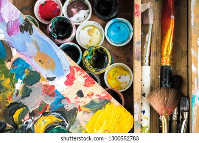 Paints of different colors and dirty brushes on the easel of the artist close-up. Colorful abstract background.