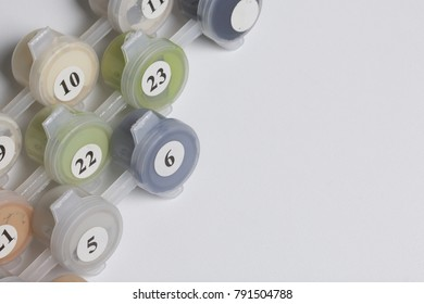 Paints for drawing by numbers. Several containers with paint are open.