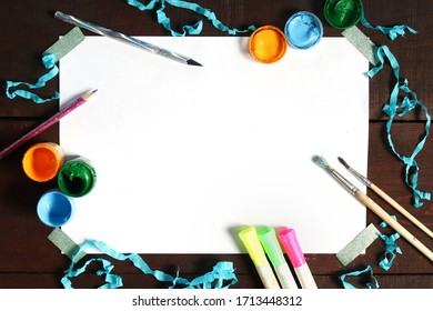 Paints, markers, pencils, brushes and a white sheet of paper. Set for drawing on paper