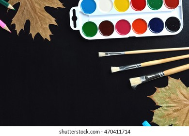 Paints, pencils and brushes on blackboard