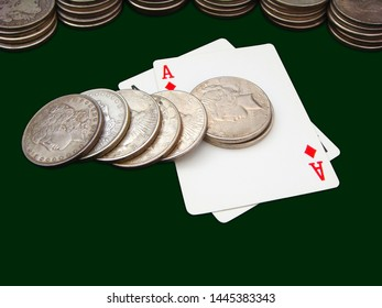 Pair Of Aces With Many Stacks Of Morgan And Peace Type Silver Dollars Over Green Background