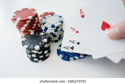 Pair of Aces playing cards balanced on white next to some poker chips. Gambling concept. Online poker during home quarantine for Coronavirus.