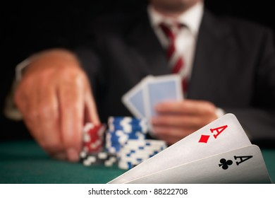 pair of aces and poker player gambling casino chips on green felt background selective focus