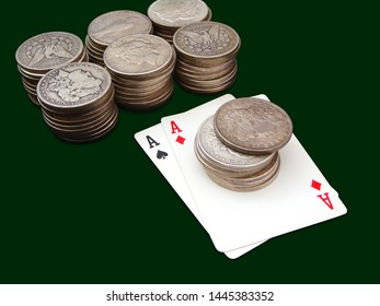 Pair Of Aces With Seven Stacks Of Morgan And Peace Type Silver Dollars Over Green Background