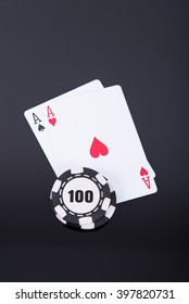 Pair of aces with a stack of 100 chips on black reflective background