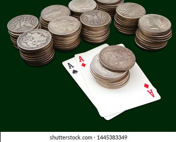 Pair Of Aces With Ten Stacks Of Morgan And Peace Type Silver Dollars Over Green Background