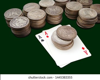 Pair Of Aces With Thirteen Stacks Of Morgan And Peace Type Silver Dollars Over Green Background