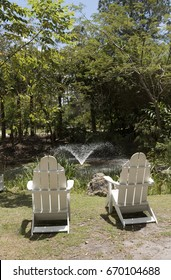 A pair of Adirondack white wooden chairs by a garden pond. Circa 2017