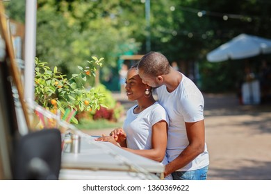 A pair of African Americans sit in an open cafe, the guy kisses a girl / copy space