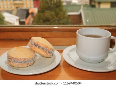 Pair of Alfajores, Traditional Latin American Sweets and a Cup of Hot Tea Served on Wooden Table by the Window, Ushuaia, Argentina