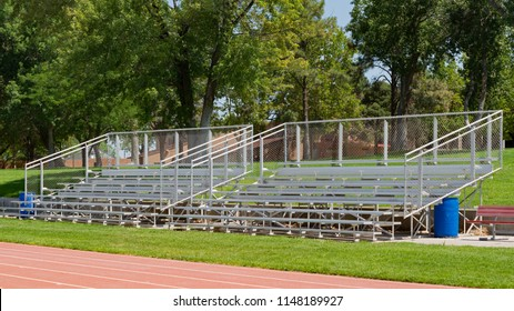 A pair of aluminum bleachers on the edge of a track with green grass around them