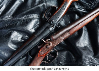 Pair of ancient hunting shotguns closeup on leather background