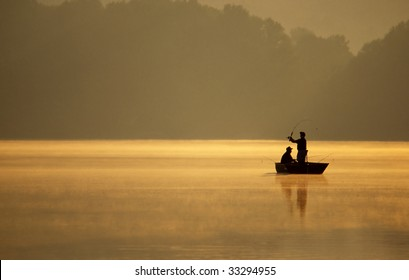 A pair of anglers enjoy a beautiful, golden, misty morning fishing on a lake.