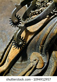 A pair of antique cowboy spurs hang from an old saddle.