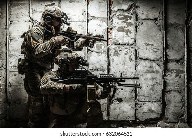 Pair of Army Rangers with rifle and machine gun moving along the concrete wall on mission. They are ready to start firing if enemy appear. Outdoor location shot