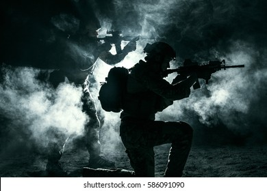 Pair of army soldiers attacking in the smoke. Backlit silhouette, toned image. Army storm concept