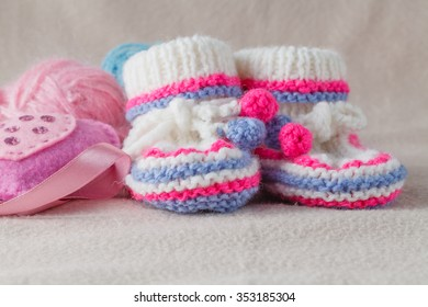 Pair of baby booties on soft felt background