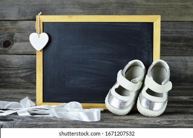 Pair of baby shoes and blank blackboard