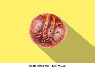 Pair of baked circle sugary brown breads with raisins on yellow table in kitchen with long shadow and copy space for your text. Flat lay