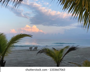 Pair of beach chairs on empty beach looking at ocean waves and clouds colored with sunrise
