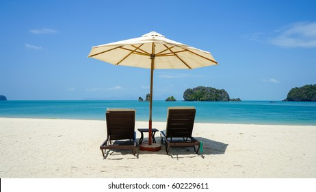 A pair of beach chairs on white sandy Tanjung Rhu beach in Langkawi Island, Malaysia.