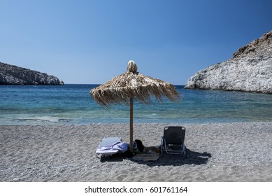 A pair of beach loungers with an umbrella, in a beach at the Greek island of Astypalaia in the Aegean Sea.