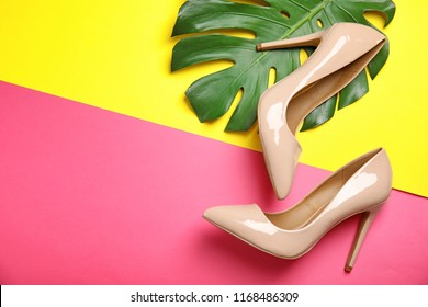 Pair of beautiful shoes with monstera leaf and space for text on color background, top view