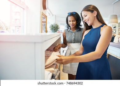 Pair of beautiful young adult female friends picking up various clothes from shelf in store
