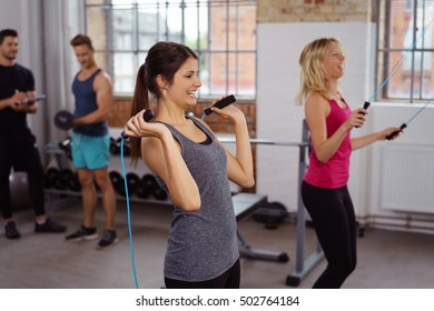Pair of beautiful young laughing ladies tank tops using jumping ropes in gym with men behind them