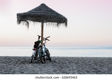 A pair of Bikes, at sunrise on the beach, placed under the straw umbrella