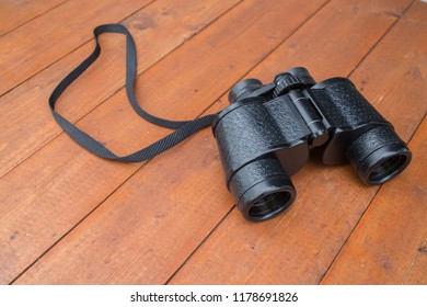 A pair of binoculars on a wooden table