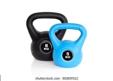 A pair of black 8 kg kettlebell and 5 kg blue kettlebell isolated on white background. Weights for a fitness training.