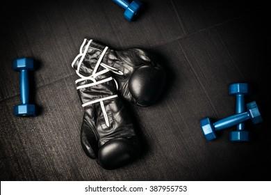 Pair of black boxing gloves, our blue dumb bells, lying on a dark tiled floor