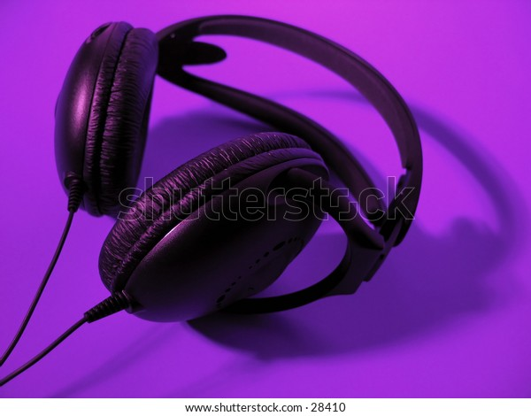 A pair of black headphones on a bright purple background.