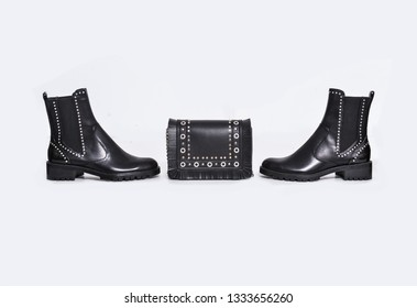 A pair black high hell boots with leather black handbag isolated