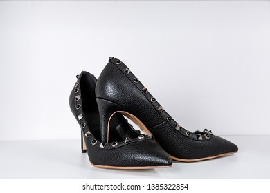pair of black high-heeled shoes with pointed toes, decorated with metal inserts against a shelf in the store