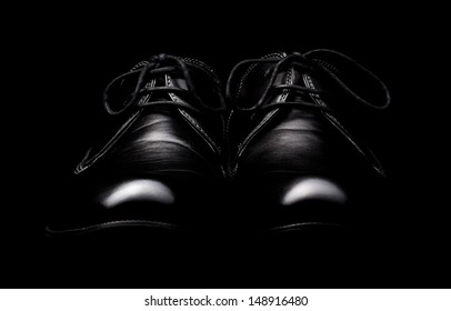 The pair of black leather shoes on a black background