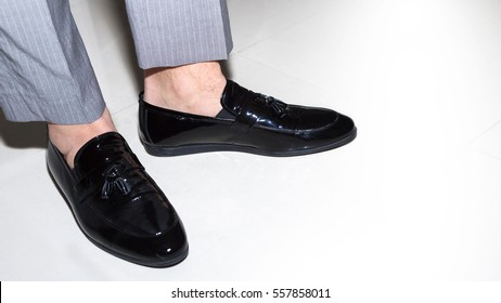 Pair of black male classic shoes on white .closeup.Man wearing short grey pants and italian shoes without socks